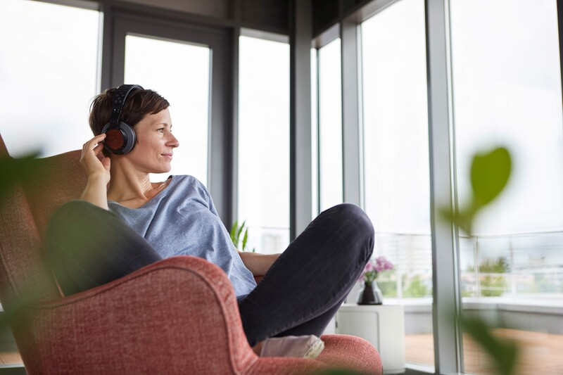 Woman with headphones sitting in an armchair and looking out the window